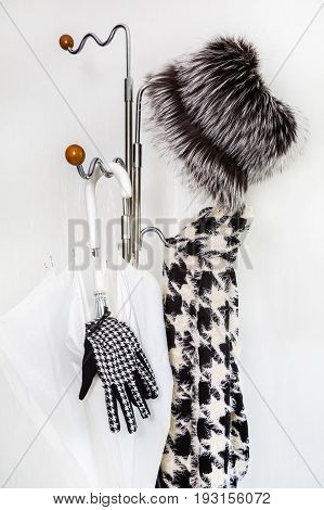 A hanger with female accessories and a white umbrella on a white background. Concept of rain.