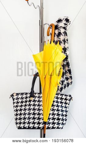 A hanger with female accessories and a yellow umbrella on a white background. Concept of rain.