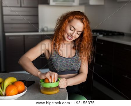 Smiling woman sitting in kitchen and squeezing the juice from orange. Horizontal indoors shot.