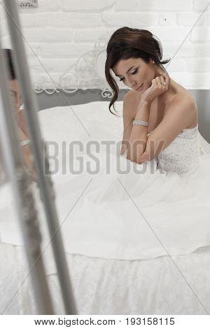 Beautiful bride sitting in wedding dress on wedding-day, daydreaming.