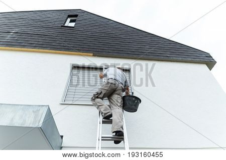 plasterer climbing up the ladder to cover the roof underside with render