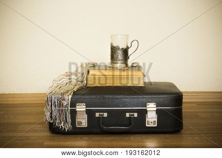 Old leather black suitcase in retro stile. Suitcase and cup of tea on the floor. Mug in the Cup holder Melchior. Cupronickel cup holder in the train. The wait before the trip. The book on the train. Vintage accessories for business. Travel bag for summer