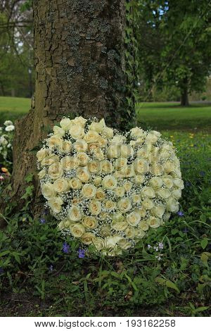Heart shaped sympathy flowers or funeral flowers near a tree