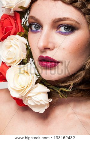 Gorgeous Woman with flowers arround her head in studio photo. Beauty and fashion. Glamour and summer