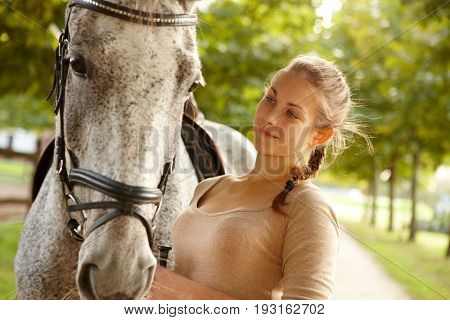 Portrait of young female rider and horse, smiling, looking tender.