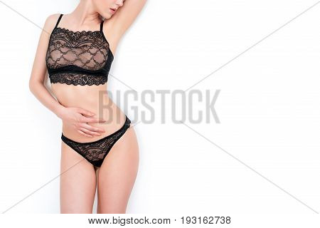 Slim, beautiful woman in lace lingerie isolated on white background. Body parts, close up of woman half body length wearing black stylish underwear. Ideal waist, perfect figure, fashionable clothes