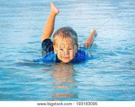 Cute boy plays in a sea