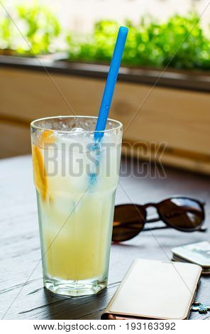 Cold lemonade with ice on a wooden background