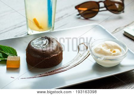 Chocolate fondant with ice cream on a wooden background