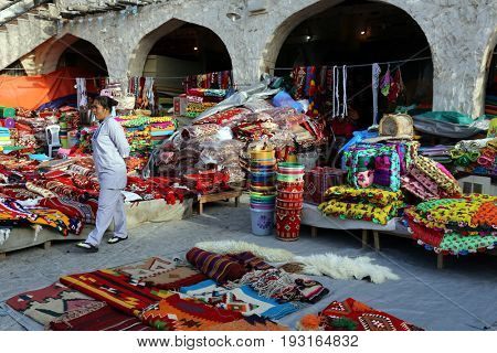 DOHA, QATAR - APRIL 9, 2017: Colourful textiles on sale at the Souq Waqif market in Doha, with an Asian saleswoman.