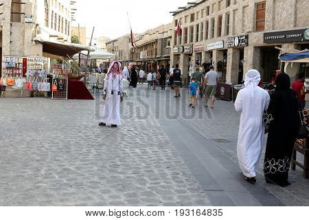DOHA, QATAR - APRIL 9, 2017: Shoppers in the main thoroughfare of Souq Waqif market in Qatar, Arabia.