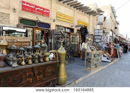 DOHA, QATAR - APRIL 9, 2017: Tourist shops in the main street of Souq Waqif market in Doha.