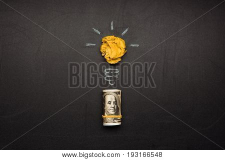 business concept made of light bulb symbol and money on blackboard
