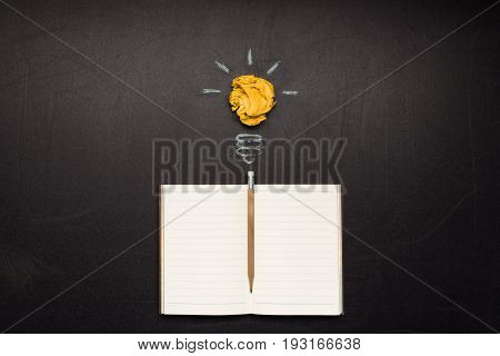 light bulb symbol and blank notebook with pencil on blackboard