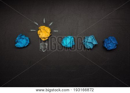 light bulb symbol and crumpled papers near by on blackboard. Business idea concept