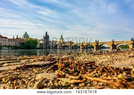 Embankment of the Vltava river and a view of the Charles Bridge in Prague, Czech Republic