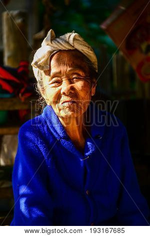 CHIANGMAI THAILAND - JANUARY 24 2015: Indigenous senior woman in light and shadow looking to visitors in Mae Chaem of Chiangmai Thailand