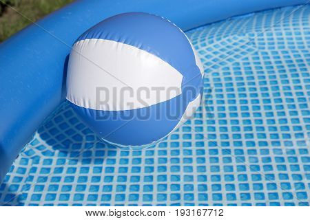 Blue and white beach ball floating in a swimming pool