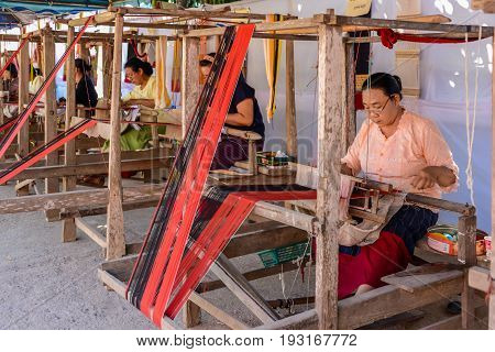 CHIANGMAI THAILAND - JANUARY 24 2015: Indigenous women are demonstrating weaving fabric in 22nd Traditional Skirt Fabric and The Indigenous Product and Culture Festival in Mae Chaem of Chiangmai Thailand