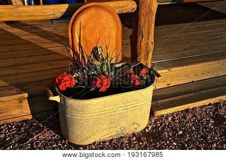 The rays of the morning sun shows the patina of an old boiler for heating water serving as a flower pot for geraniums on a deck