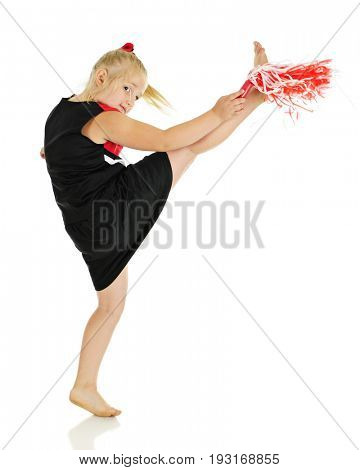 A young elementary cheerleader, barefoot and in uniform, looking at the viewer as she kicks high with her pom pom. On a white background.