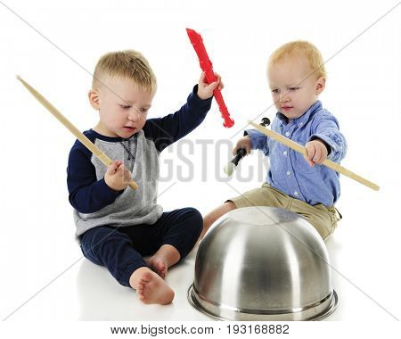 A two-toddler rhythm and music band. Both boys hold a recorder and drumstick in their raised hands, and upside down