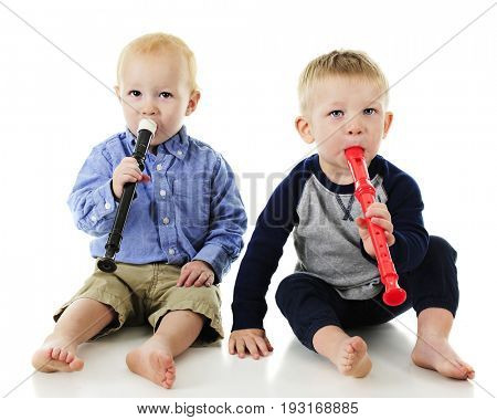 Two adorable toddlers making music together on plastic recorders.  On a white background.