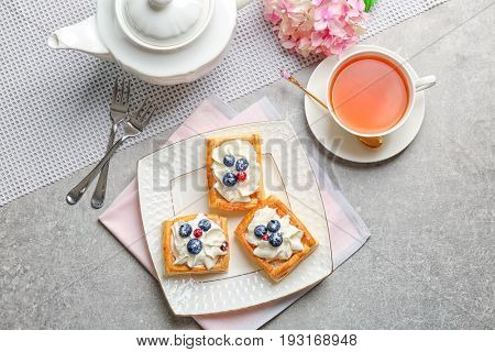 Plate with pastries, flatware and cup of tea on grey table