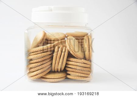 A plastic transparent container of many crackers with cream inside on the white background