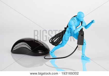Blue Male Figurine Dragging A Computer Mouse Across White Table. Corporate Job, Slavery, And Debt Co