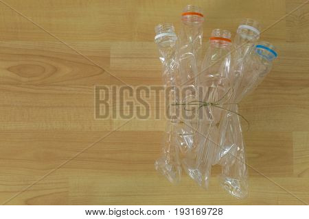 Group of emptied recyclable clear plastic mineral soda water bottles tied together on wooden background with copyspace