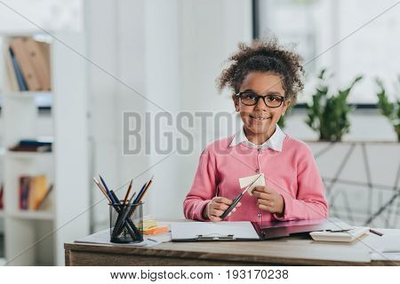 Adorable Little Girl In Eyeglasses Holding Scissors And Smiling At Camera