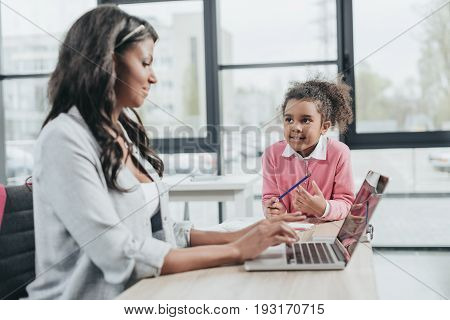 Side View Of Businesswoman Typing On Laptop While Daughter Getting Bored, Work And Life Balance Conc