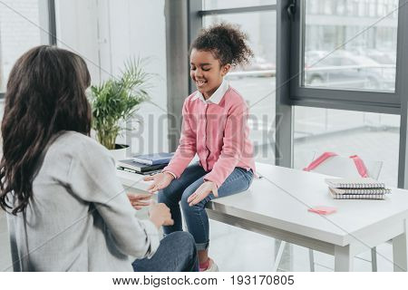 Mother Playing Pat A Cake With Little Daughter In Business Office, Work And Life Balance Concept