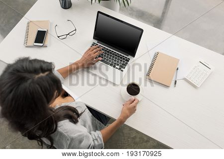 Overhead View Of Young Businesswoman Drinking Coffee While Working On Laptop At Office
