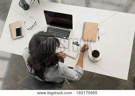 Overhead View Of Young Businesswoman Using Calculator On Workplace At Office
