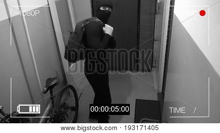 surveillance camera caught the robber in a mask running off with a bag of loot, shows the camera the middle finger.