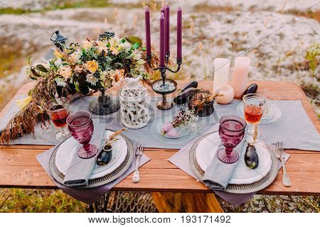 A wooden table is served for two, on the table there are compositions of flowers, candles, cutlery and glasses for wine. Wedding area. Details. Outdoors