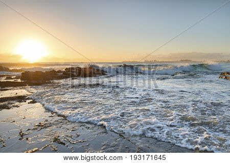 Ocean sunrise and surf hitting the rocks at Currumbin Rock, Gold Coast