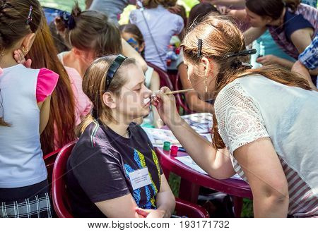 Zaporizhia/Ukraine- May 28, 2017: Charity Family festival:  face painting children activity.  Teen girl getting funny animal watercolor mask painted on her face.