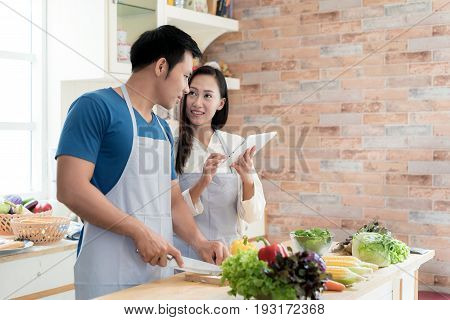 Asian beautiful young husband and wife searching menu recipe in digital tablet in kitchen at home. Happy love couple and technology concept.
