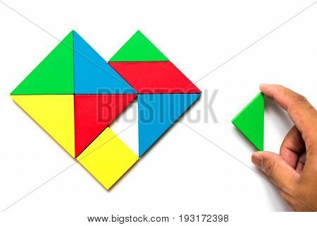 Colorful wooden tangram puzzle in heart shape wait to fulfill with triangle shape on white background