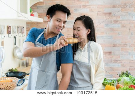 Asian beautiful young couple is feeding bread smiling while cooking in kitchen at home. Happy love couple in home.