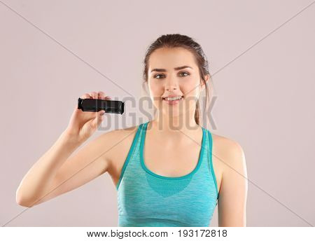 Beautiful young woman with energy bar on color background. Diet concept