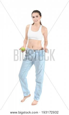 Beautiful young woman in oversized jeans and with apple on white background. Diet concept