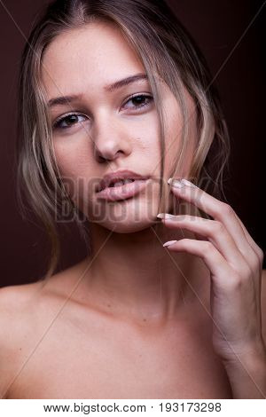 Portrait of beautiful woman with no makeup on brown background in studio photo