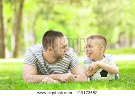 Father and son with soccer ball lying on green grass in park