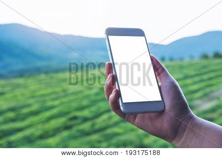 Mockup image of a hand holding and showing white smart phone with blank screen at outdoor and green nature background