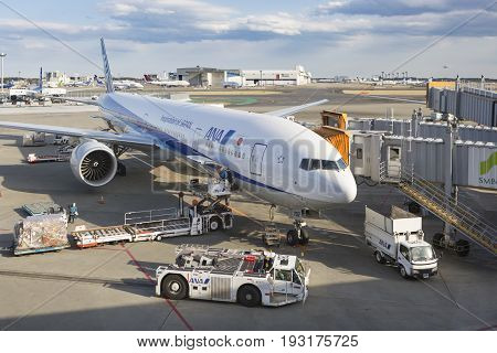 TOKYO-MARCH 25 2016 : Workers load bags onto a ANA (All Nippon Airways) Boeing 777 parked at Narita International Airport is an international airport serving the Greater Tokyo Area of Japan.