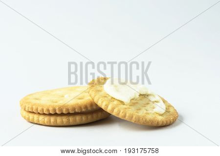 Two crackers with cream on the white background